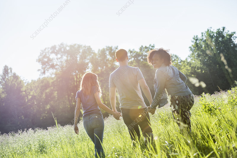 Three people walking in summer meadow