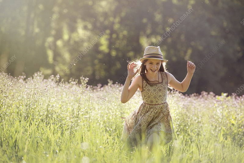 A young girl walking in a field