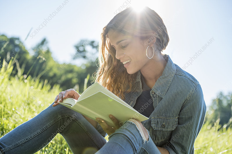 A young woman sitting reading a book
