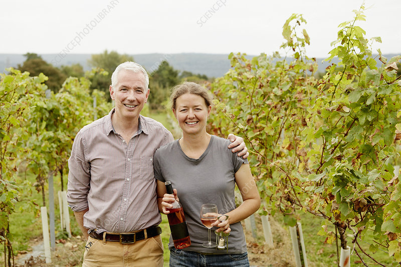 A couple standing among rows of vines