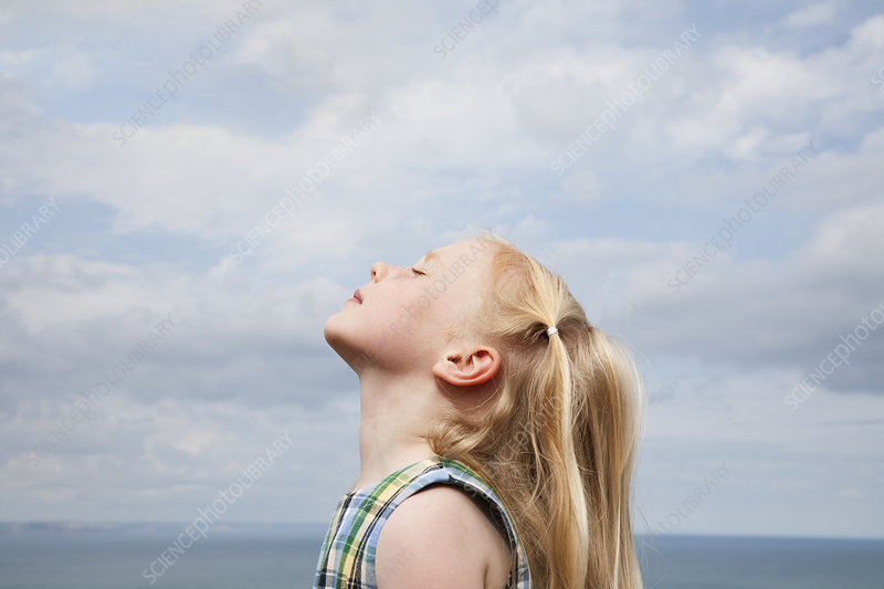 A young girl raising her face to the sun