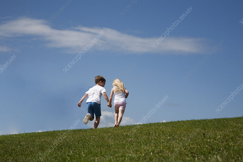Two children running up a hill