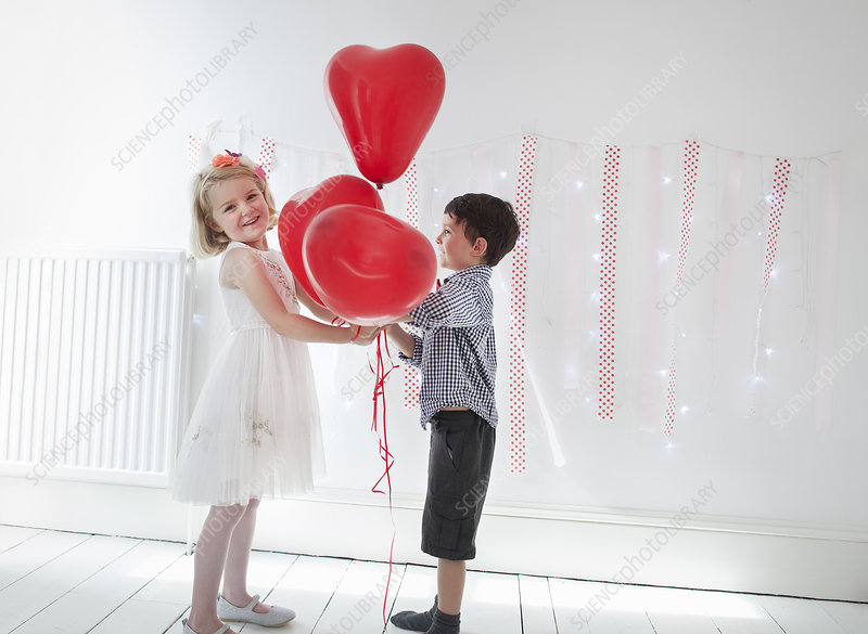 Young boy and girl with red balloons