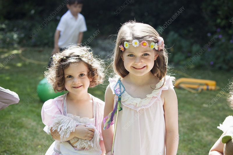 Two smiling young girls at a garden party