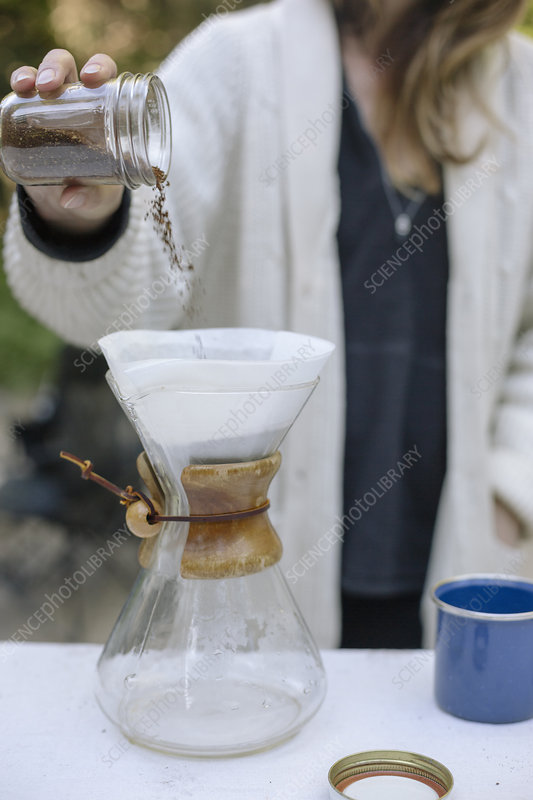 Woman pouring ground coffee from a jar