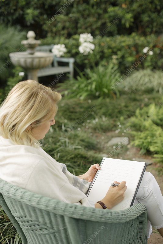 Woman sitting in a garden, writing