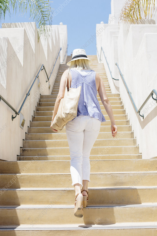 Blond woman walking up a staircase