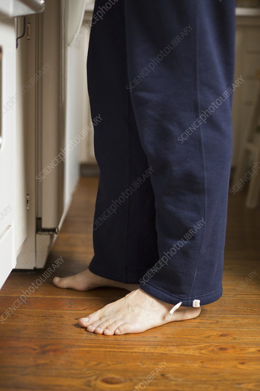 Barefoot man standing in a kitchen