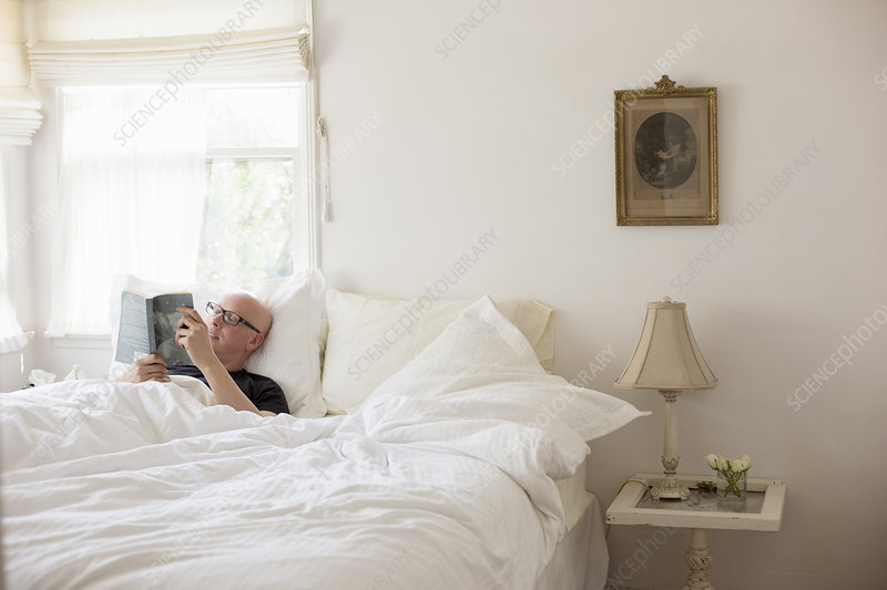 Man lying in a bed reading