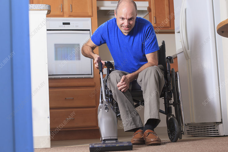 Man in wheelchair vacuuming his house