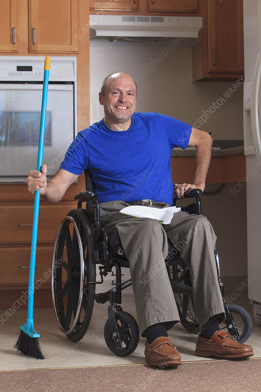 Man in wheelchair cleaning his house