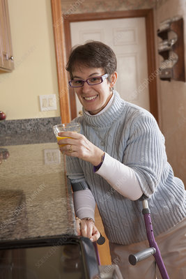 Woman using crutches in her kitchen