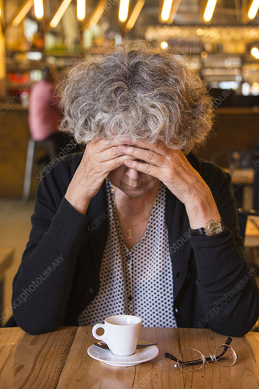 Senior woman in cafe with head in hands