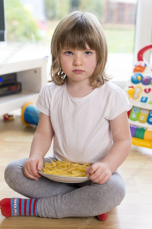 Girl sitting on floor with french fries