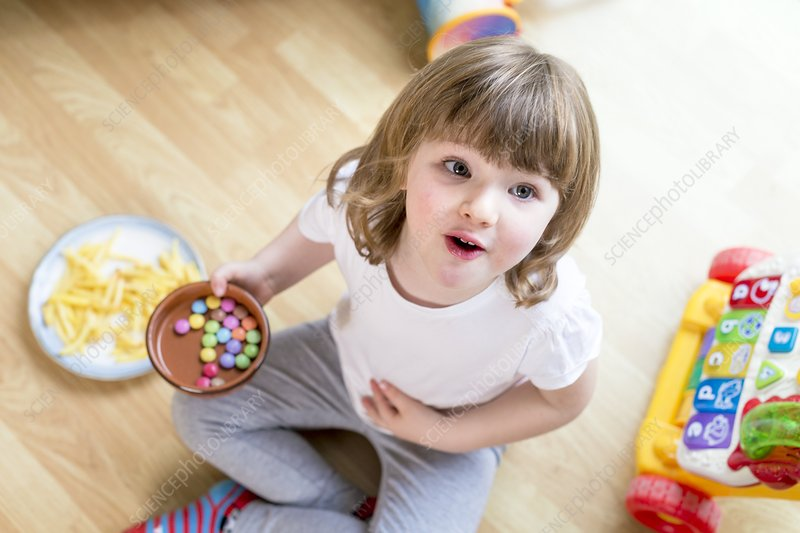 Girl sitting on floor with bowl of sweets