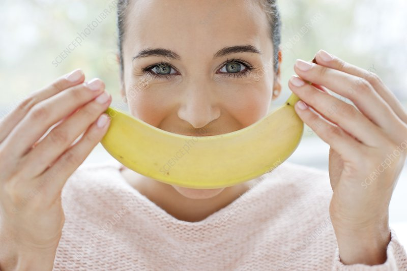 Woman holding a banana in front of face