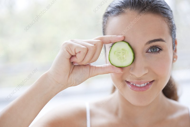 Woman with slice of cucumber