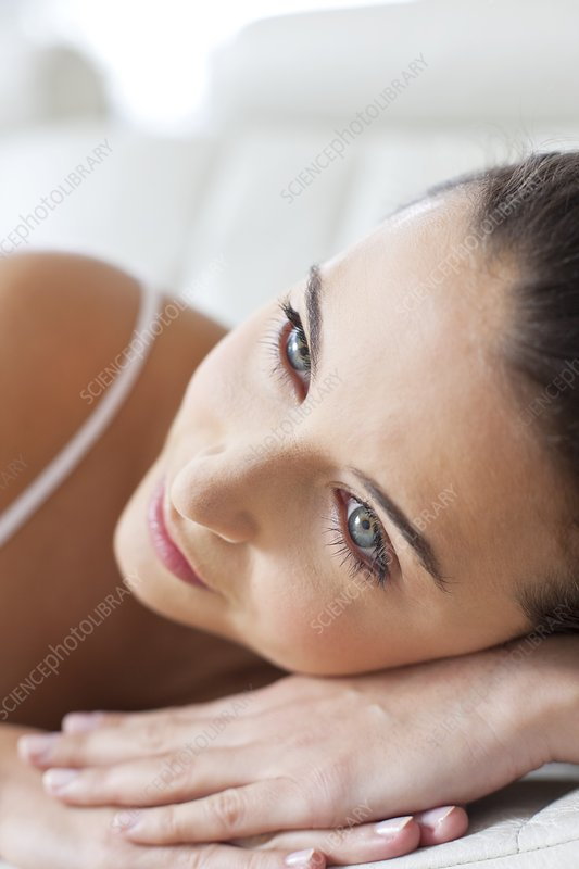 Woman lying with head on hands