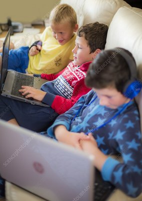 Three boys using laptops sitting on sofa