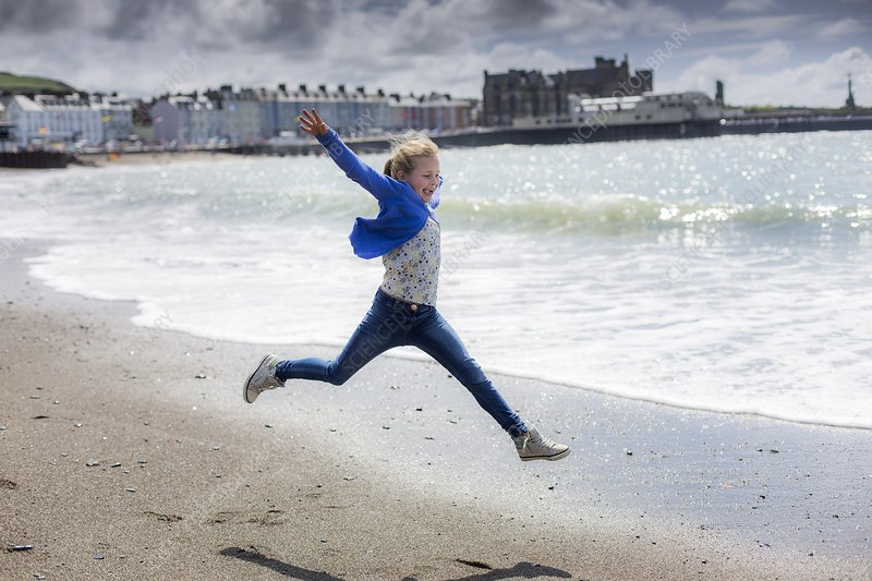 Girl leaping on beach