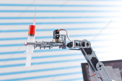 Robotic arm holding syringe