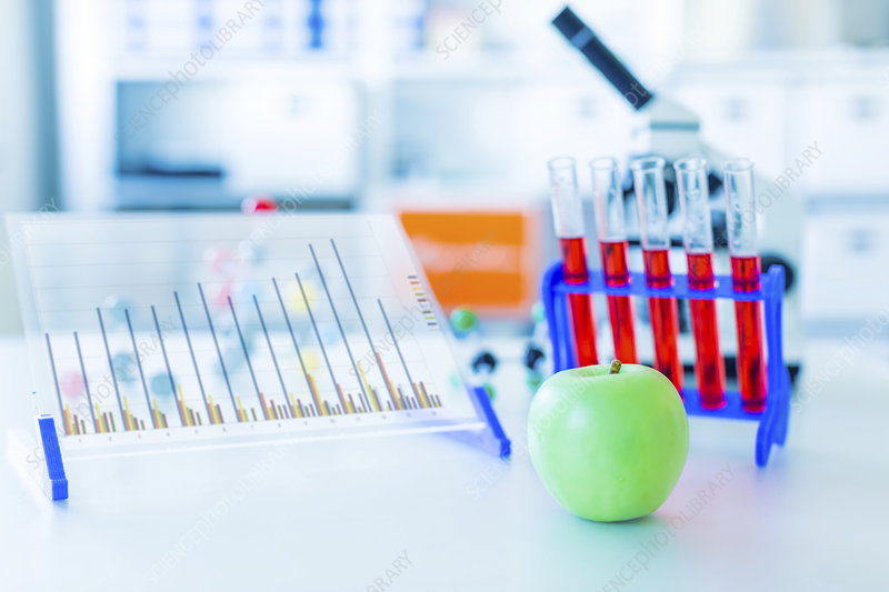 Apple and test tubes in lab