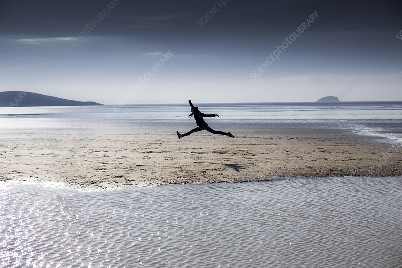 Person leaping on a beach