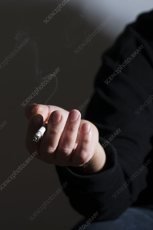 Person holding a cigarette, smoking