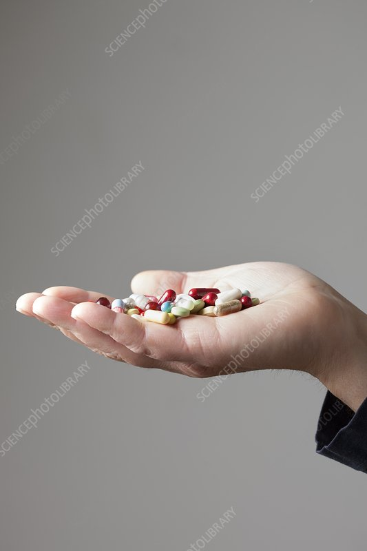 Person holding pills on palm of hand