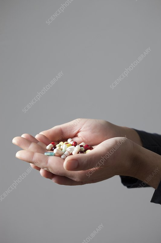 Person holding pills in cupped hands
