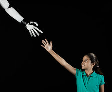 A girl reaching to touch a robotic hand