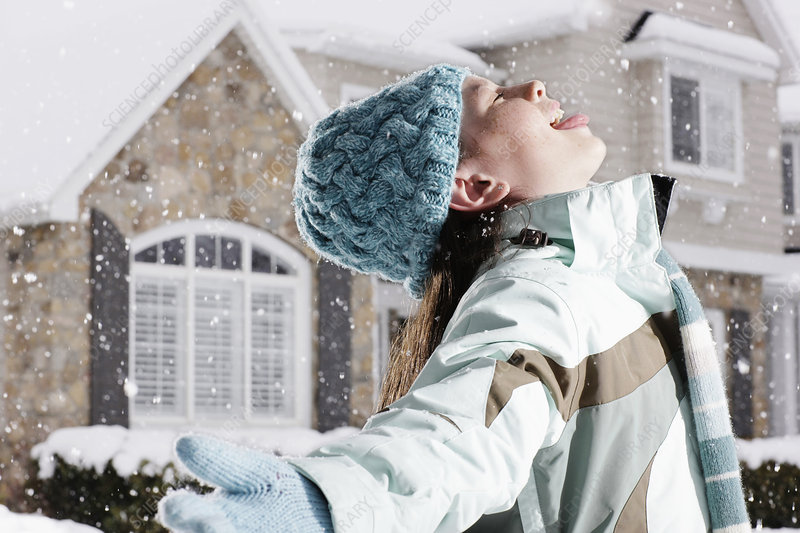 A girl catching snow in her open mouth