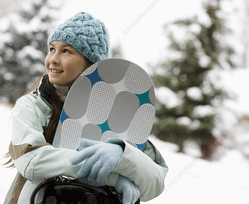 A girl carrying a snowboard