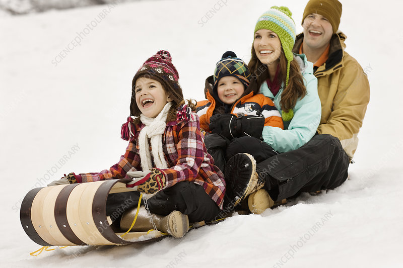 A family sitting on sledges on the snow