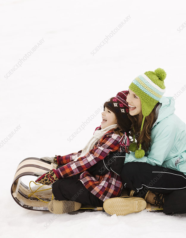 Two children on a sledge on the snow