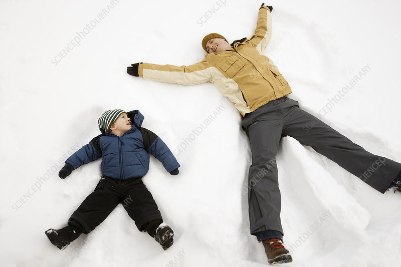 Man and a child making snow angel shapes