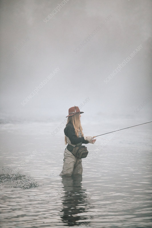 Woman fisherman fly-fishing in waders
