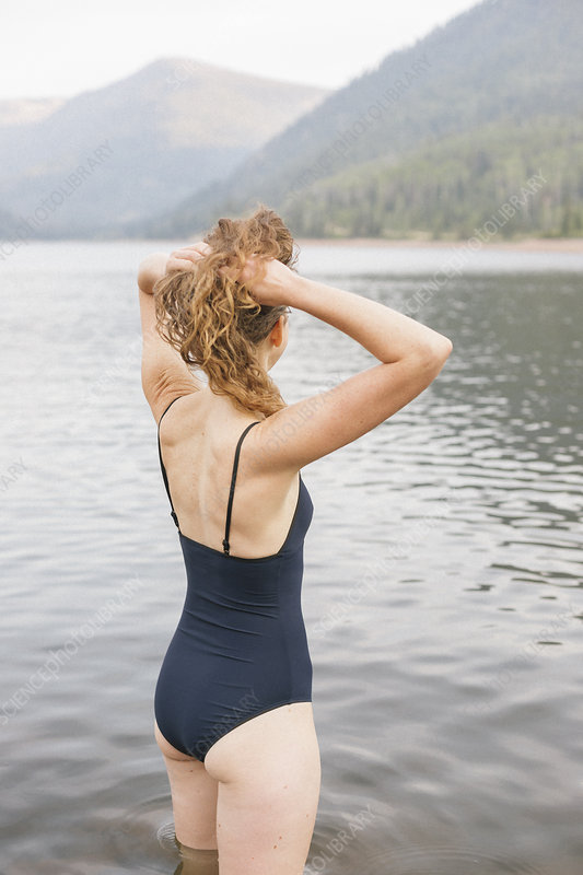 Woman in a swimsuit wading into water