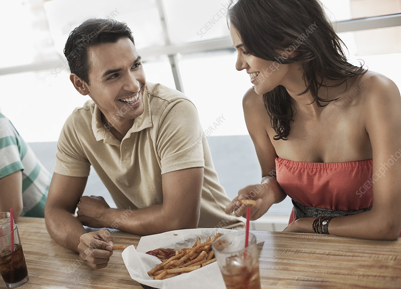 Couple sharing fries in a diner