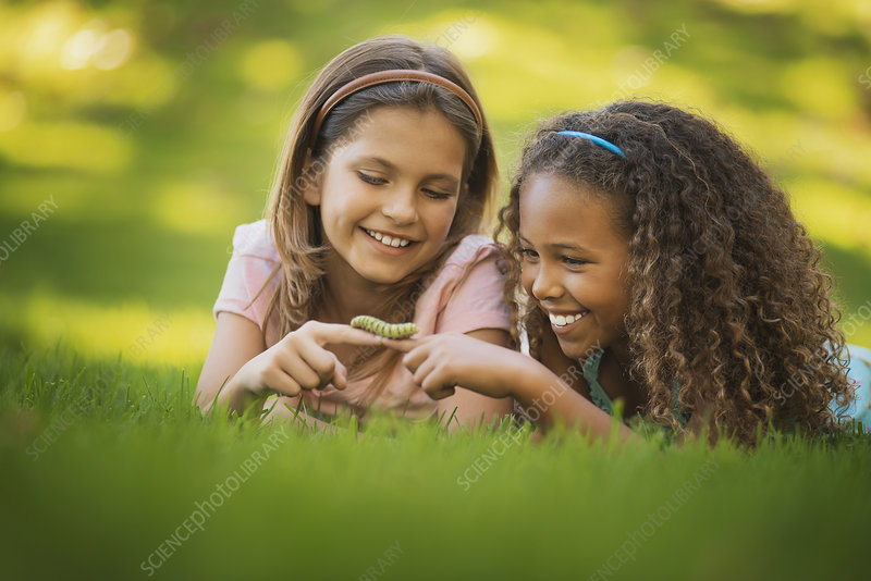 Two girls one holding a green caterpillar