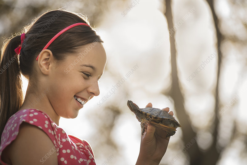 A girl holding a small turtle