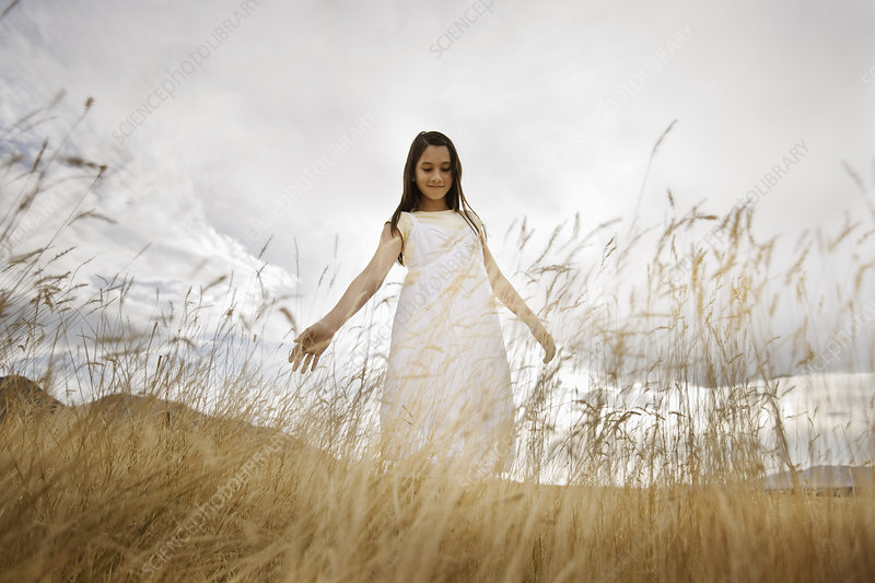 A girl in a white dress in long grass