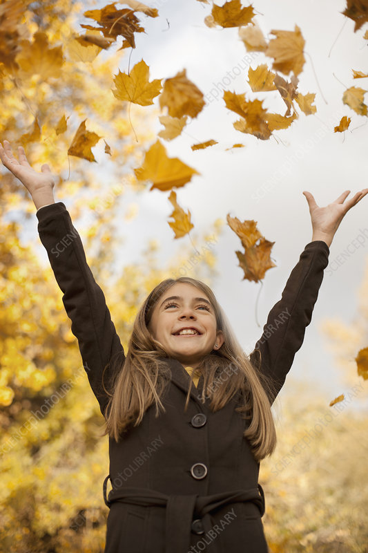 A girl throwing fallen autumn leaves