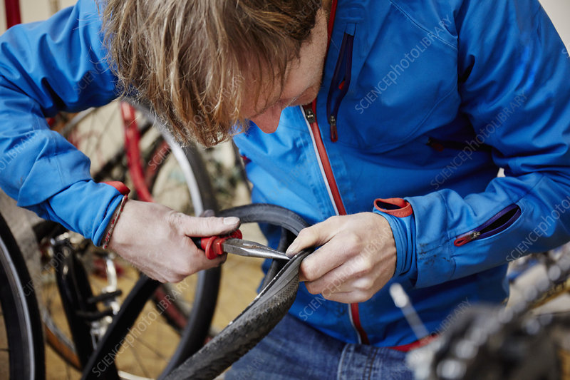 A young man working repairing a bicycle