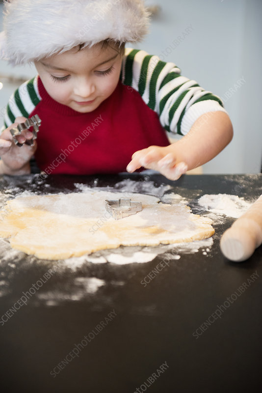 A boy making Christmas biscuits