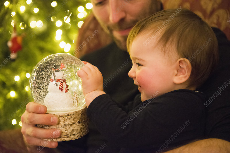 A man and child looking at a snowglobe