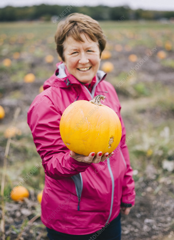 A mature woman holding out a pumpkin