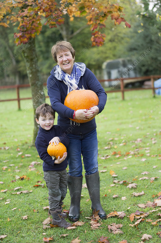 Woman and boy holding pumpkins