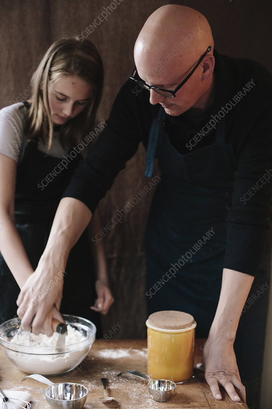 A man and girl mixing ingredients in bowl