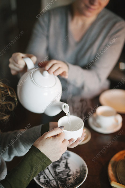 Woman pouring tea from a teapot